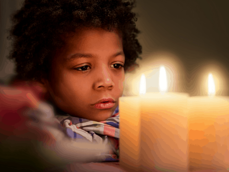 sad child in candle light